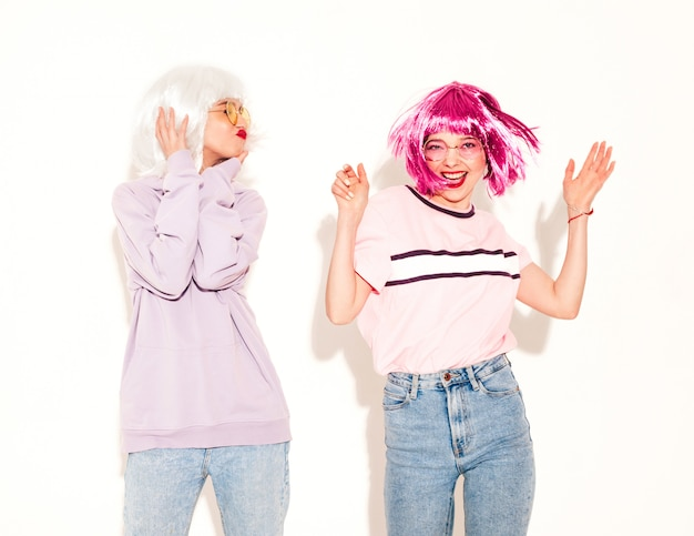 Due giovani ragazze sorridenti sexy dei pantaloni a vita bassa in parrucche e labbra rosse belle donne d'avanguardia in vestiti modelli modelle che posano vicino alla parete bianca in studio che impazzisce e che balla