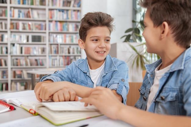 Due giovani ragazzi felici che studiano insieme in biblioteca
