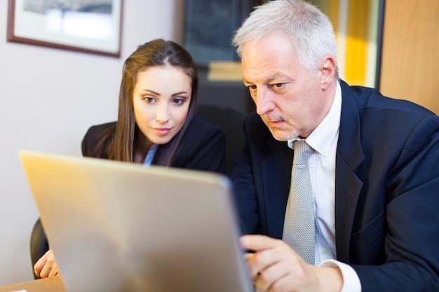 Due giovani soci in affari che discutono i piani o le idee alla riunione