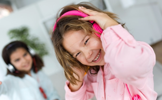 Due giovani sorelle che ascoltano la musica e ballano a casa.