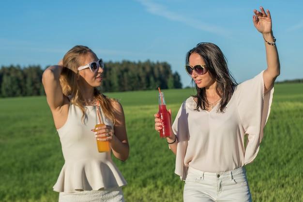 Due giovani sorelle snelle con occhiali e capelli ricci sorridono e bevono un cocktail alcolico o analcolico attraverso una cannuccia da una bottiglia in una giornata di sole estivo sorridente