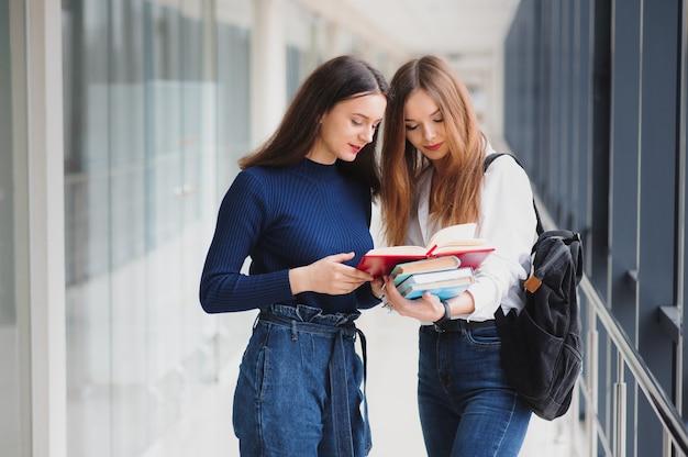 Due giovani studentesse in piedi con libri e borse nel corridoio