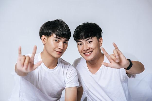 Due giovani uomini amorevoli si guardano l'un l'altro e fanno una mano di simbolo d'amore.
