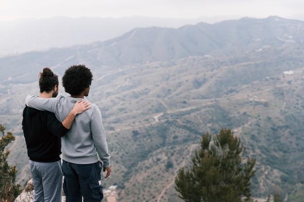 Due giovani uomini che guardano il paesaggio di montagna