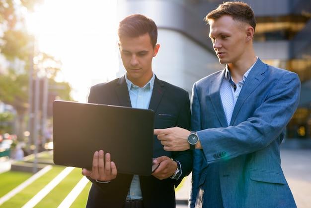 Due giovani uomini d'affari belli che lavorano insieme al di fuori dell'edificio