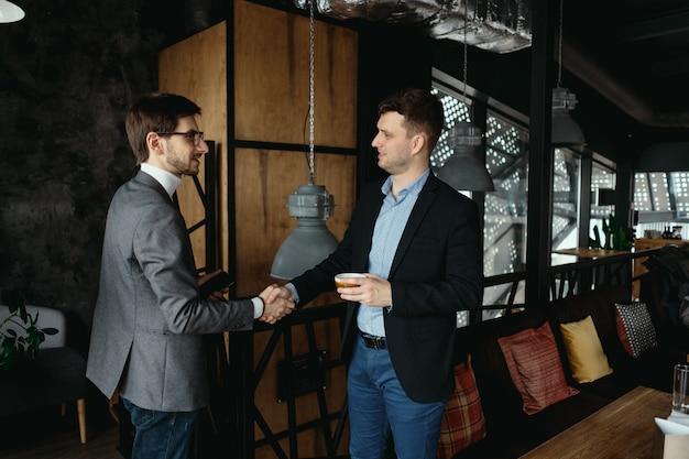 Due giovani uomini d'affari che si salutano, stringendo la mano