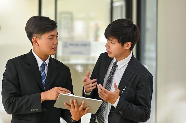 Due giovani uomini d'affari si consultano e si incontrano con i discorsi d'affari.