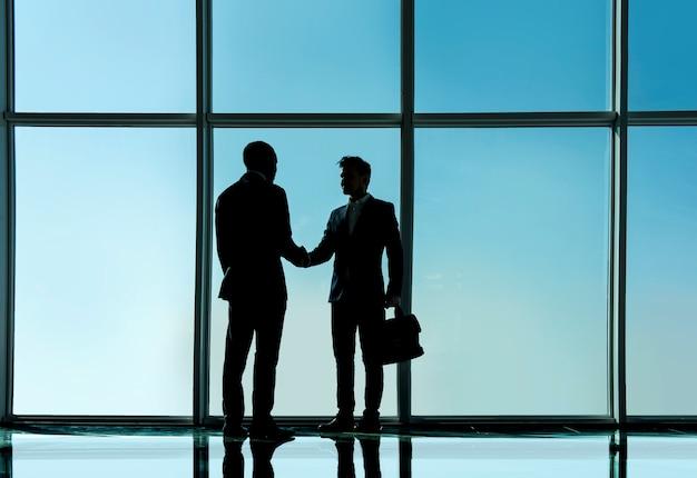 Due giovani uomini d'affari sono in piedi in ufficio moderno.