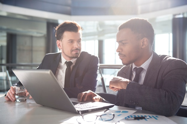 Due giovani uomini d'affari stanno lavorando con il laptop.