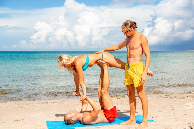 Due giovani uomini e donne sulla spiaggia facendo yoga fitness si esercitano insieme. elemento acroyoga per forza ed equilibrio