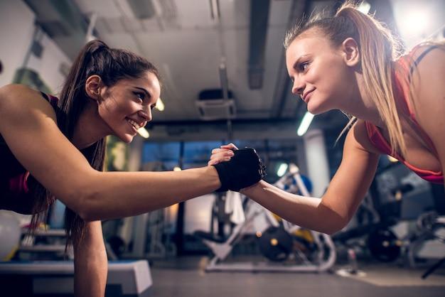 Due giovani womans attivi sportivi focalizzati attraenti sorridenti motivati mentre fanno push up e tenendosi per mano nella palestra moderna.