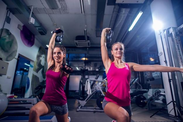 Due giovani womans in forma in una palestra facendo squat mentre si tiene il peso in una mano.
