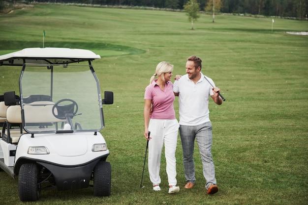 Due golfisti professionisti, una donna e un uomo vanno insieme alla buca successiva. gli amanti si abbracciano e sorridono, hanno un appuntamento