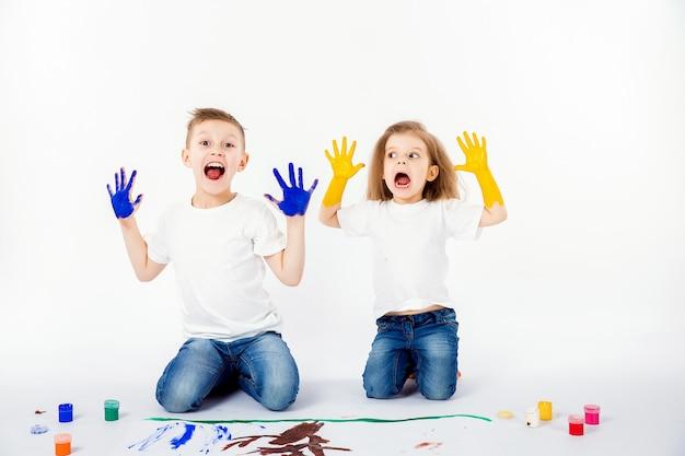 Due graziosi amici del bambino ragazzo e ragazza stanno disegnando le immagini dalle pitture. mostrando le mani in vernice