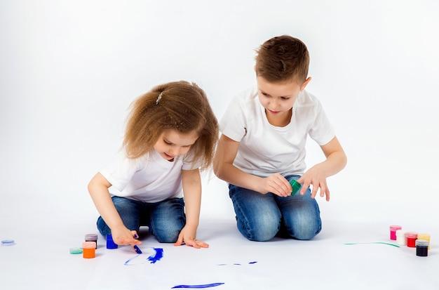 Due graziosi amici del bambino ragazzo e ragazza stanno disegnando le immagini dalle pitture