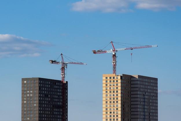 Due gru a torre sullo sfondo di due case in costruzione