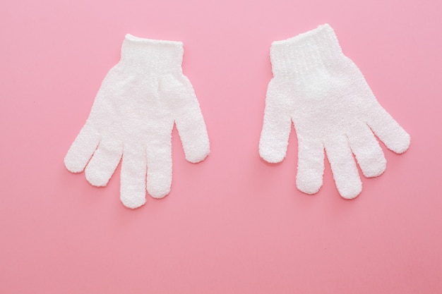 Due guanti da massaggio esfolianti per la doccia su sfondo rosa. guanti da usare nella doccia per massaggi e scrub.