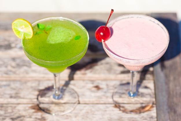 Due gustosi cocktail sul tavolo di legno in spiaggia bianca tropicale