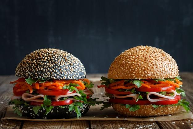 Due hamburger freschi appetitosi scuri e chiari con semi di sesamo, primo piano, con verdure fresche (pomodoro, peperone dolce), carote coreane, prezzemolo e prosciutto. nero sfocato.