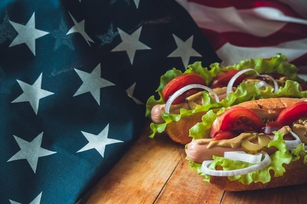 Due hot dog freschi su una tavola di legno, bicchieri con cola e bandiera americana