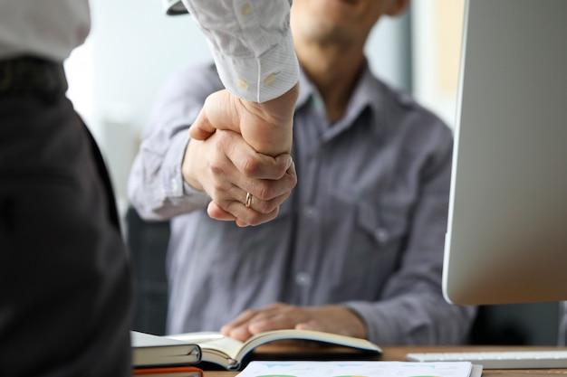 Due impiegati maschii che stringono le mani al primo piano del posto di lavoro