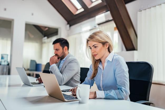 Due imprenditori che lavorano su computer portatili in ufficio luminoso coworking.