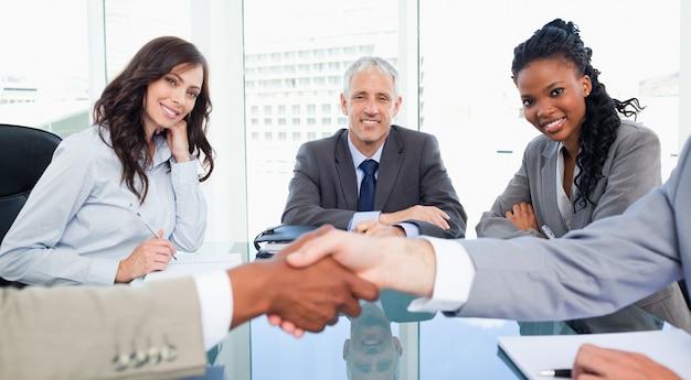 Due imprenditrici e il loro manager guardando i dirigenti si stringono la mano