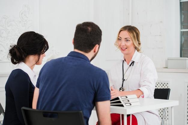 Due infermiere o medici graziosi delle giovani donne che parlano con il cliente femminile nel loro ufficio