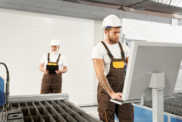 Due ingegneri in caschi e uniformi in lavorazione