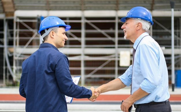 Due ingegneri si stringono la mano in un cantiere
