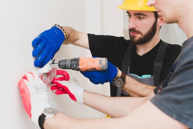 Due lavoratori che installano la spina di parete