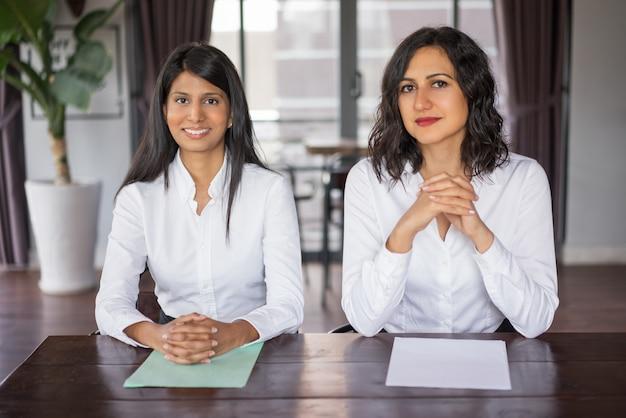 Due lavoratrici positive che si siedono allo scrittorio in ufficio moderno.