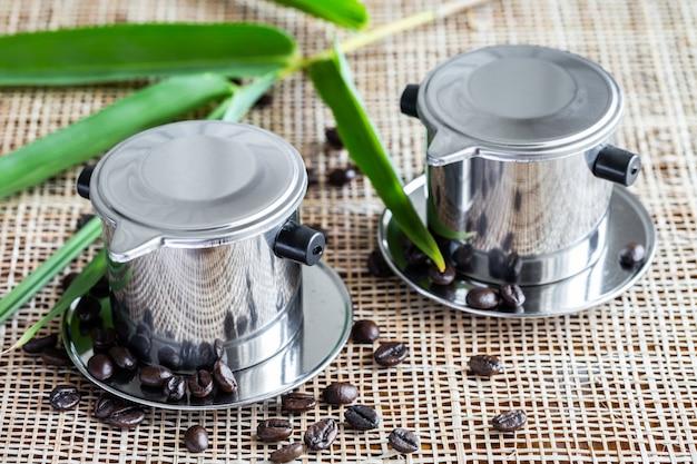 Due macchine da caffè con chicchi di caffè interi sparsi su tovaglietta.