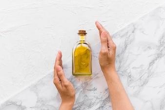 Due mani che coprono la bottiglia di olio d'oliva su due vivaci fondali