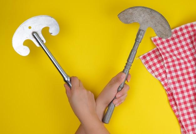 Due mani che tengono i coltelli da cucina taglienti d'annata per carne e verdure