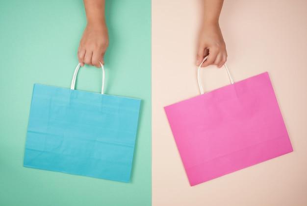 Due mani che tengono i sacchetti della spesa di carta sul fondo astratto di colore