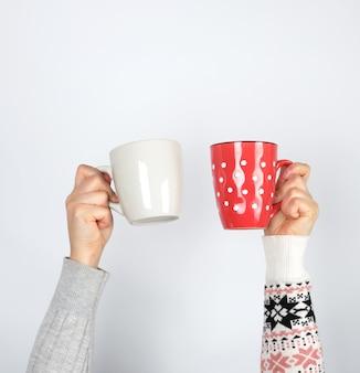 Due mani che tengono le tazze di ceramica su una priorità bassa bianca, spazio della copia