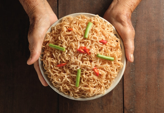 Due mani che tengono una tazza di noodles istantanei