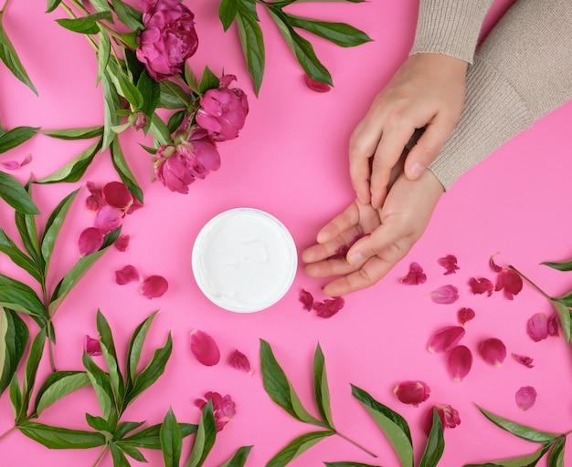 Due mani di una ragazza con la pelle liscia e un vaso con una crema densa