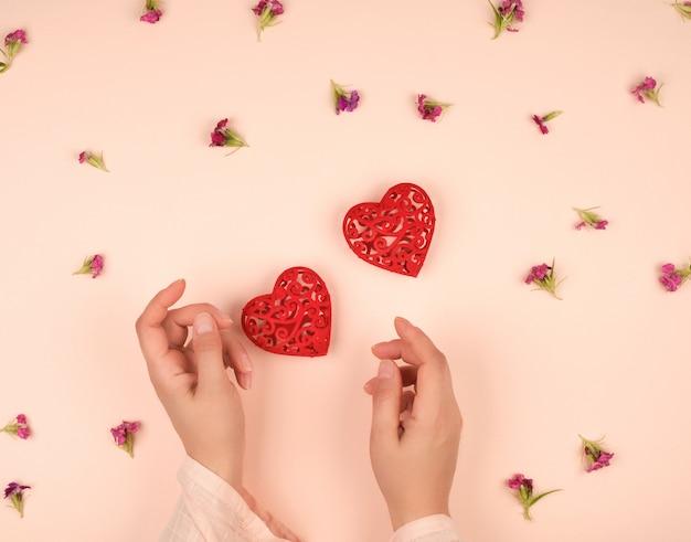 Due mani femminili e cuori rossi