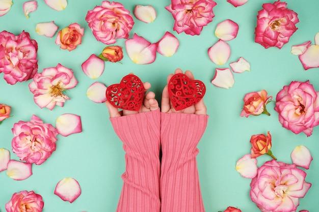 Due mani femminili tengono cuori rossi