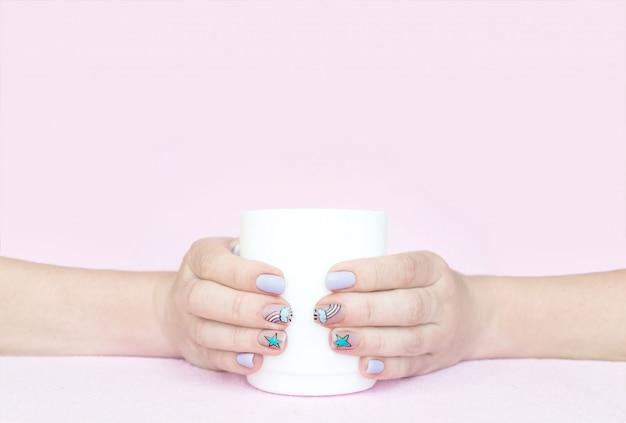 Due mani femminili tengono la tazza bianca su fondo rosa