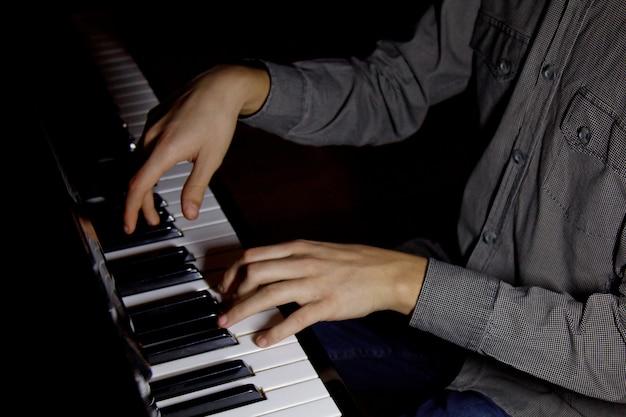 Due mani maschili al pianoforte. i palmi si trovano sui tasti e suonano lo strumento a tastiera nella scuola di musica. lo studente impara a giocare. pianista mani. sfondo nero scuro.