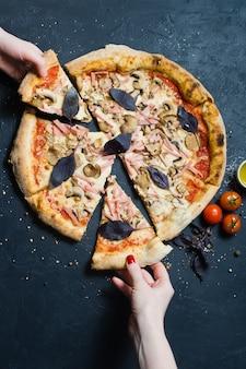 Due mani prendono un pezzo di pizza appena sfornata.