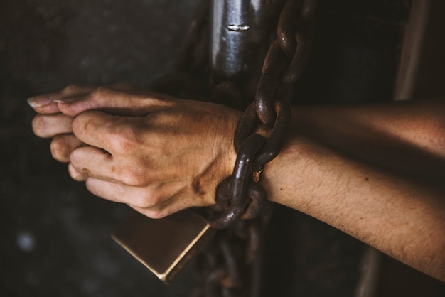 Due mani sono incatenate con il lucchetto sul prigioniero delle sbarre
