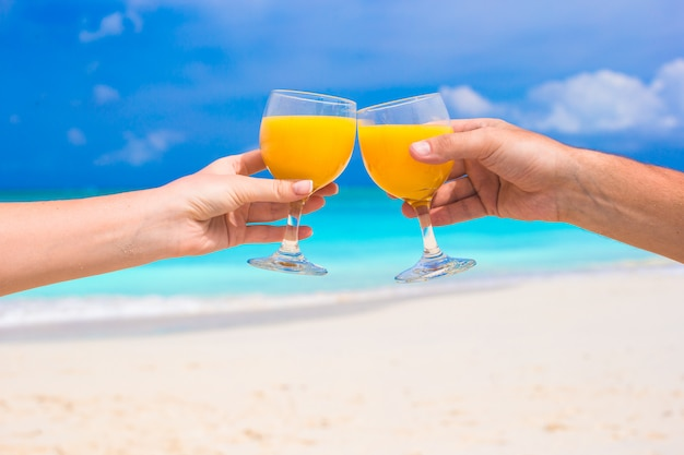 Due mani tengono i bicchieri con succo d'arancia in spiaggia