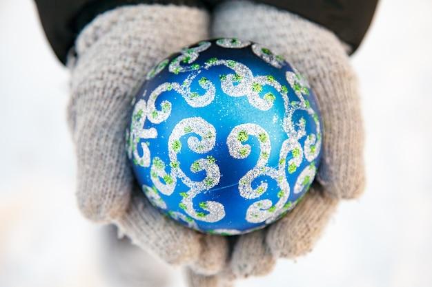 Due mani tengono un ornamento di natale blu.