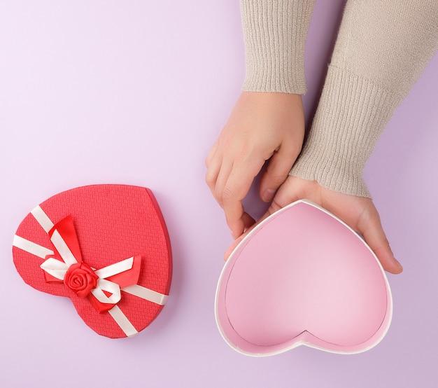 Due mani tengono una scatola rossa aperta di carta a forma di cuore su uno sfondo viola
