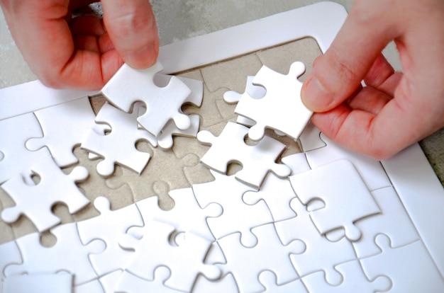 Due mano che tiene un pezzo di puzzle incompleto puzzle bianco sul tavolo
