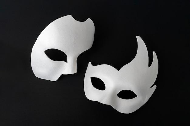 Due maschere bianche mascherate su sfondo nero.